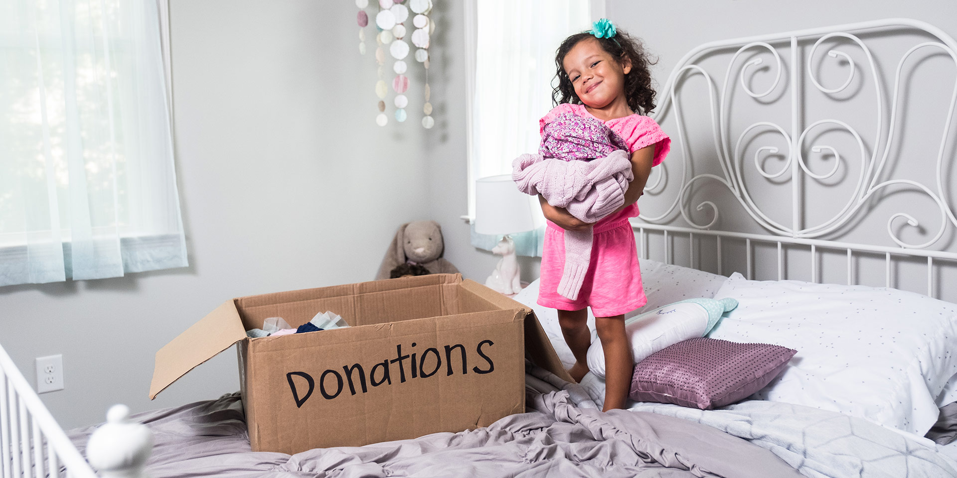 A young girl is excited to bring her donations to Goodwill.
